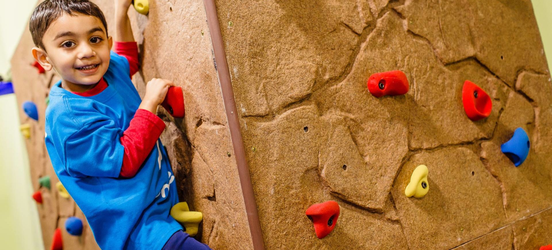 Boy climbing a rock wall at Tumbles