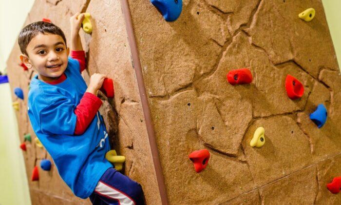 kid climbing on a rock tumbles playground